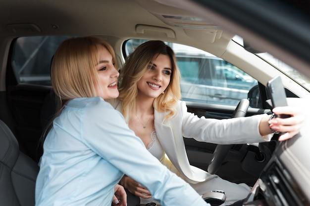2人のビジネス女性が新しい車で自分撮りを取る