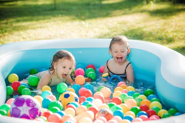 夏の晴れた日に膨脹可能なプールでおもちゃで遊ぶ2歳の小さな女の赤ちゃん