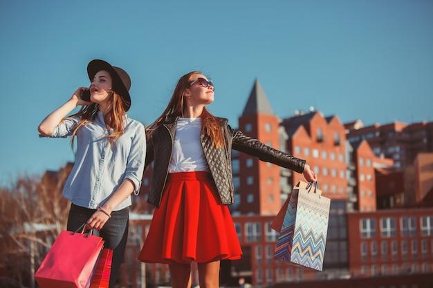 晴れた日に街の通りに買い物袋と歩いている2人の女の子