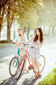 公園で自転車を持つ2人の若い女の子
