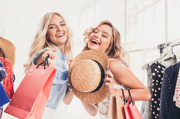 2人の若いきれいな女性がドレスを見て、店で選択しながら試着