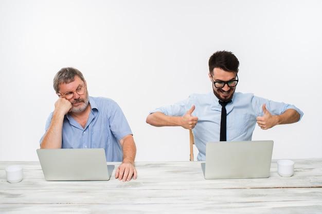 白のオフィスで一緒に働く2人の同僚