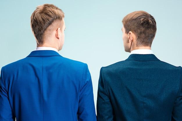 スーツを着た2人のスタイリッシュな若者。背面から見た背面図。