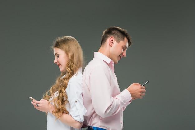 ビジネスコンセプトです。灰色の背景に携帯電話を保持している2人の若い同僚