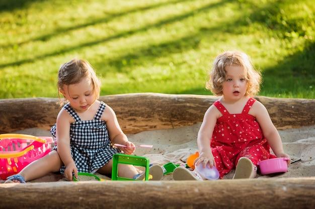 砂でおもちゃを遊んでいる2人の小さな女の赤ちゃん