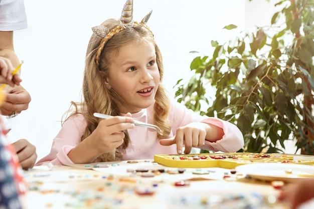 子供のためのモザイクパズルアート、子供たちの創造的なゲーム。 2人の姉妹がモザイクを遊んでいます。