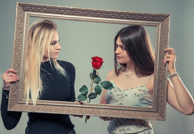 画像とローズのフレームを持つ2つの美しい若い女性の肖像画