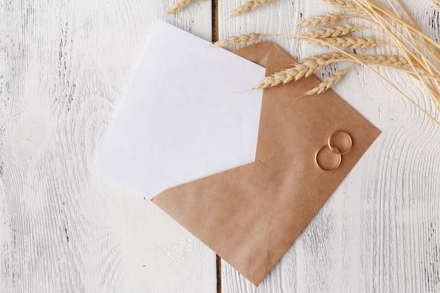 結婚式の招待状用の2つのリングが付いているクラフト封筒