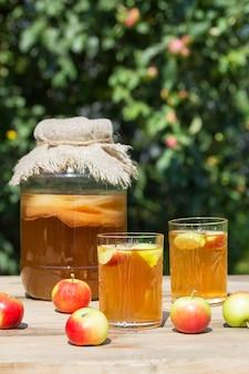 木製のテーブルの庭で日当たりの良い夏の日に、ガラスの瓶と手前のリンゴと一緒に2つのグラスで発酵させた昆布茶ドリンク。素朴なスタイル。
