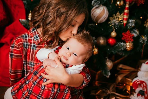 2人の姉妹がクリスマスツリーの横に抱擁します。