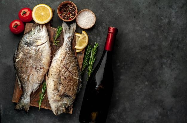 2つのディナー-ドラド魚のグリル、まな板、スパイスとワインのボトル、石の背景にグラスで提供しています