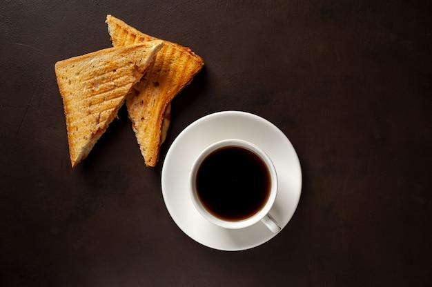 2つのサンドイッチと石の背景にコーヒー