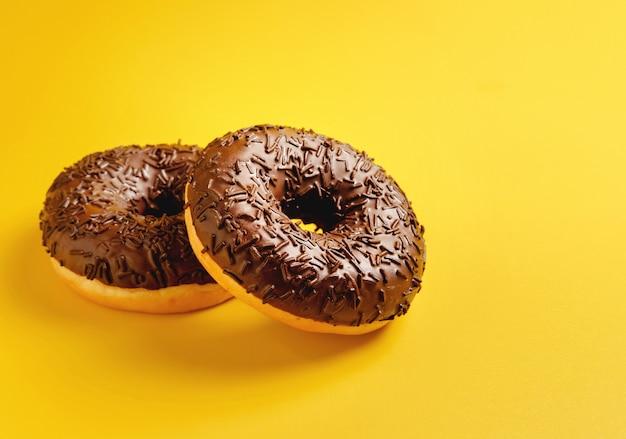 黄色の背景の上面に2つのチョコレートドーナツ