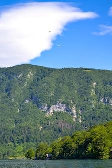 2つのハンググライダーが山から降りてきます。山の風景、湖、山脈–アルプスのスロベニアのボーヒニ湖。