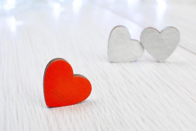 明るい木製の2つの灰色とは対照的に、赤い木製のハート。報われぬ愛の概念、不運なバレンタインデー