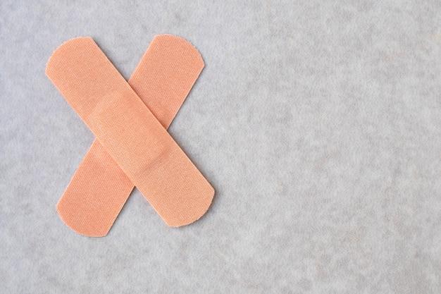 中立的な背景に十字形の2つの医療絆創膏。外傷によるパッチ。