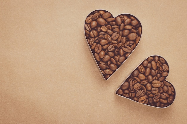 2 сердца кофейных зерен на коричневой предпосылке.