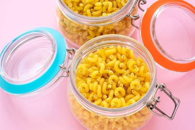 生パスタが入った2つのガラス瓶。黄色いマカロニの鍋