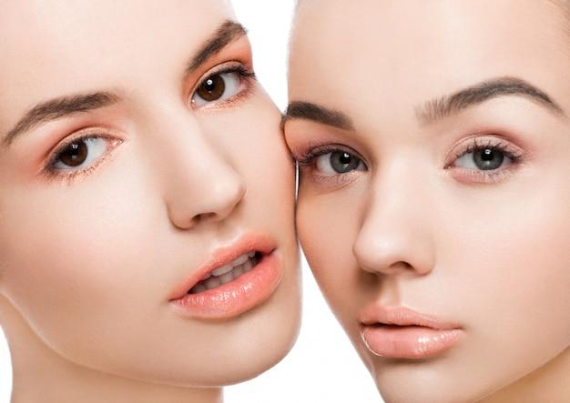 白い背景の上の自然の美しさの化粧品で2つの美しいモデル