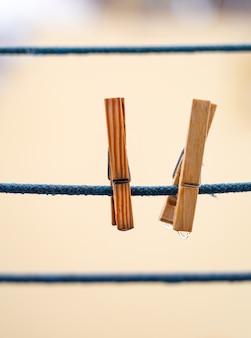 掛かる水滴が付いている青いロープで2つの木製洗濯はさみ