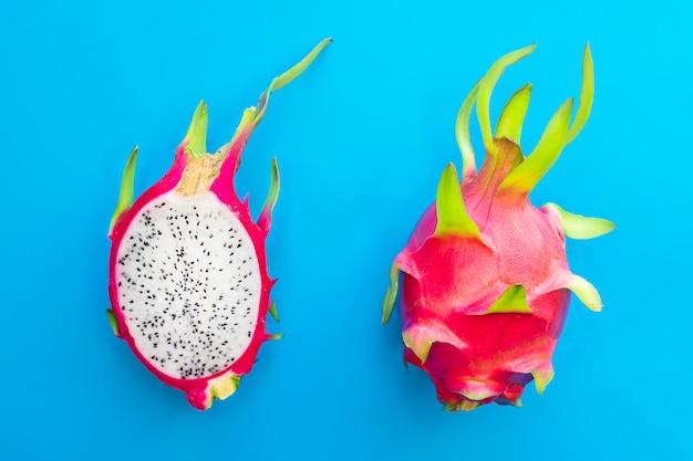 Плод дракона, 2 двух спелых питайи или экзотическая тропическая питайя, сладкий кактус, разрезанный пополам и целый фрукт на синем. вид сверху. лето, здоровые свежие продукты, веганский или вегетарианская диета концепции.