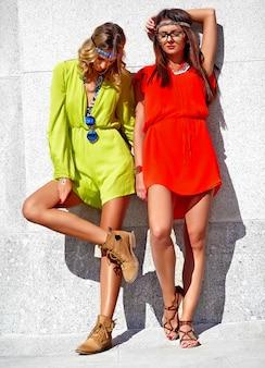 明るくカラフルな流行に敏感な服で夏の晴れた日に2つの若いヒッピー女性モデルのファッションポートレート