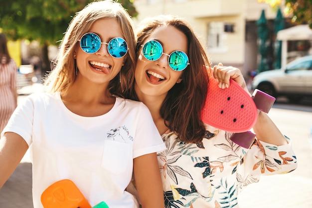 ペニースケートボードのポーズと流行に敏感な服で夏の晴れた日に2つの若いスタイリッシュな笑みを浮かべてヒッピーブルネット