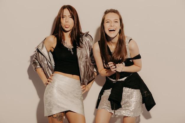 トレンディな夏服で流行に敏感な女の子を笑顔2つの若い美しいブロンド。セクシーな屈託のない女性がスタジオの壁の近くでポーズします。