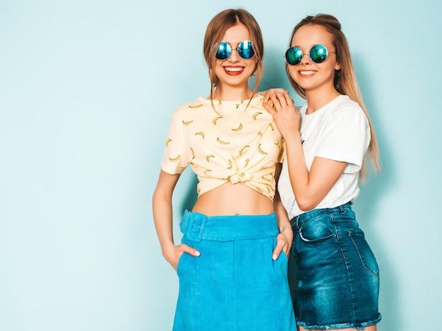 トレンディな夏のジーンズの2人の若い美しい笑顔金髪流行に敏感な女の子は服をスカートします。