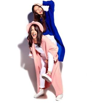 Фасонируйте портрет 2 усмехаясь моделей женщин брюнет в вскользь пальто битника лета изолированном на белизне. девушки держат друг друга на спине