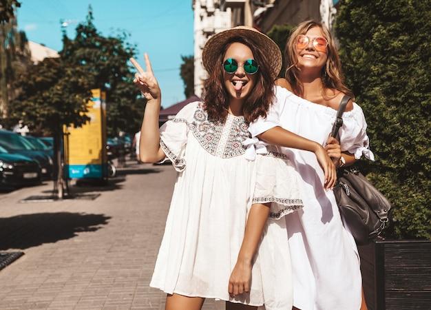 夏の晴れた日に2人の若いスタイリッシュなヒッピーブルネットとブロンドの女性のファッションの肖像画。白い流行に敏感な服を着たモデル。梨花のポーズ