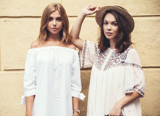 夏の晴れた日の黄色の壁に近いポーズ白いヒップな服で2つの若いスタイリッシュなヒッピーブルネットとブロンドの女性モデルのファッションの肖像画。化粧なし