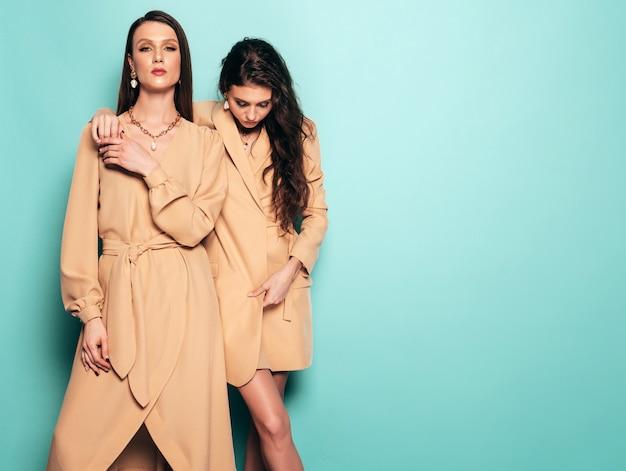 素敵なトレンディな夏服の2人の若い美しいブルネットの少女。スタジオで青い壁に近いポーズセクシーな屈託のない女性