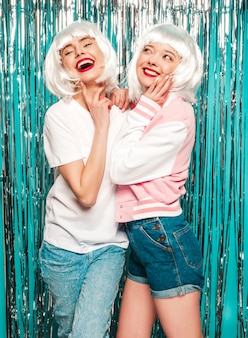 白いかつらと赤い唇の2人の若いセクシーな笑顔の流行に敏感な女の子。夏服夏の美しいトレンディな女性