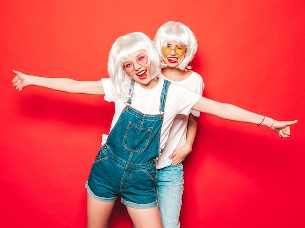 白いかつらと赤い唇の2人の若いセクシーな流行に敏感な女の子。夏の服の美しいトレンディな女性。サングラスのスタジオ夏の赤い壁に近いポーズの屈託のないモデル