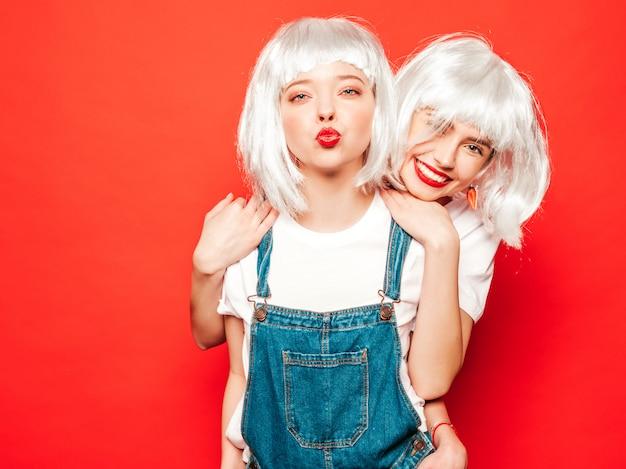白いかつらと赤い唇の2人の若いセクシーな笑みを浮かべて流行に敏感な女の子。