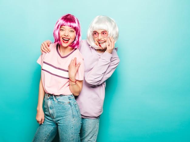 かつらと赤い唇の2人の若いセクシーな笑顔の流行に敏感な女の子。夏の服の美しいトレンディな女性。スタジオの青い壁に近いポーズの屈託のないモデル