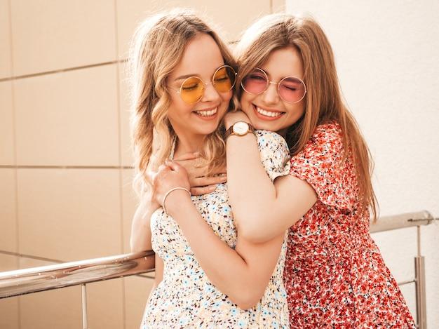 トレンディな夏のサンドレスで2人の若い美しい笑顔の流行に敏感な女の子。セクシーな屈託のない女性がサングラスで通りの背景にポーズします。楽しくてハグするポジティブモデル