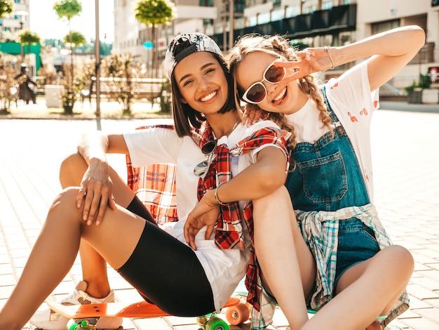 カラフルなペニースケートボードと2人の若い笑顔の美しい女の子。通りの背景に座っている夏の流行に敏感な服の女性。楽しくてクレイジーになるポジティブモデル。ピースサインを表示