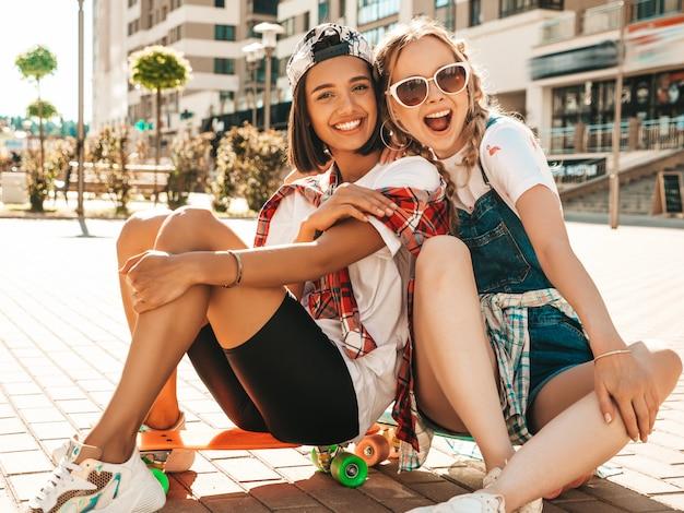 カラフルなペニースケートボードと2人の若い笑顔の美しい女の子。通りの背景に座っている夏の流行に敏感な服の女性。楽しくてクレイジーになるポジティブモデル