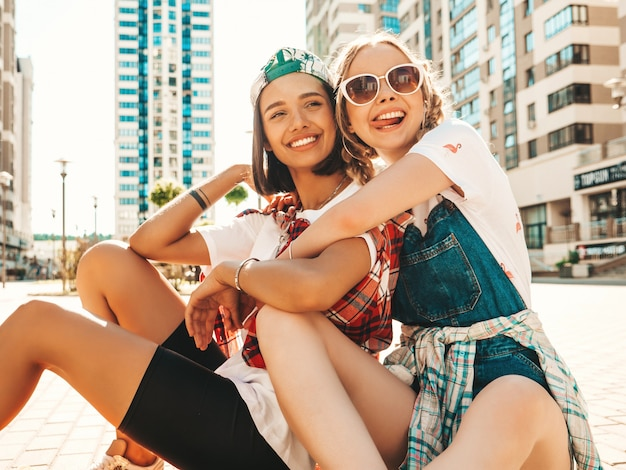 カラフルなペニースケートボードと2人の若い笑顔の美しい女の子。通りの背景に座っている夏の流行に敏感な服の女性。楽しくてクレイジーになるポジティブモデル。舌を示す