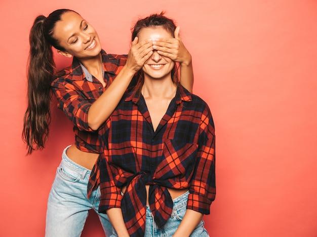 トレンディな同様の格子縞のシャツとジーンズの服の2人の若い美しい笑顔ブルネット流行に敏感な女の子。スタジオで青い壁の近くでポーズセクシーな屈託のない女性。彼女の友人の目を覆ってハグ