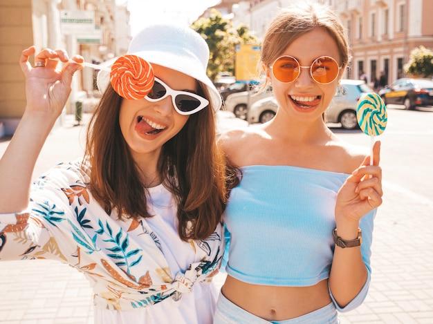 トレンディな夏服とパナマ帽子の2人の若い美しい笑顔流行に敏感な女の子。