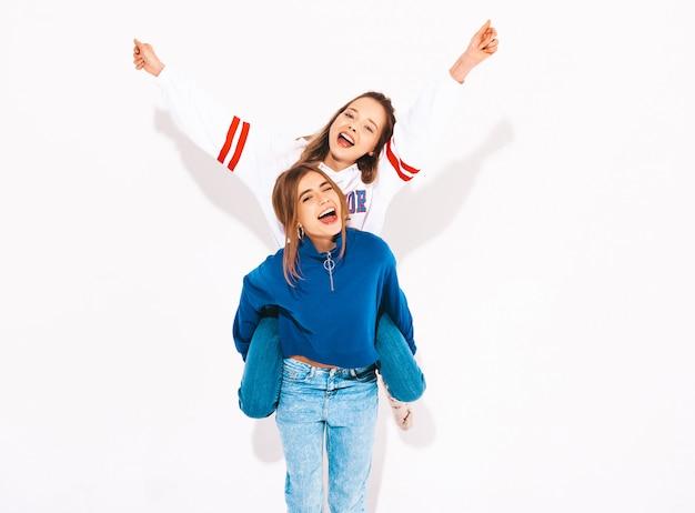 トレンディな夏服の2人の若い美しい笑顔の女の子。のんきな女性。彼女の友人の背中に座って手を上げるポジティブモデル