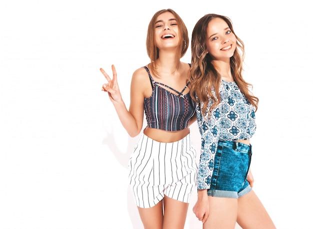 トレンディな夏服の2人の若い美しい笑顔の女の子。セクシーな屈託のない女性。ポジティブモデル