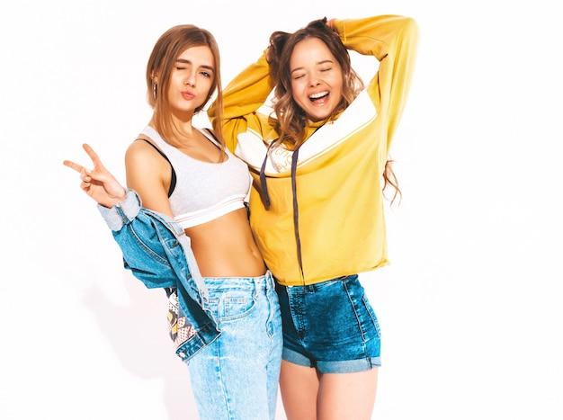 トレンディな夏のジーンズ服で2人の若い美しい笑顔の女の子。セクシーな屈託のない女性。ポジティブモデル