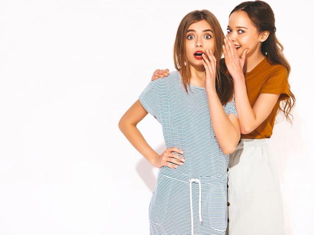 トレンディな夏のカジュアルな服で2人の若い美しい笑顔の女の子。セクシーな女性は秘密、ゴシップを共有します。驚いた顔の感情