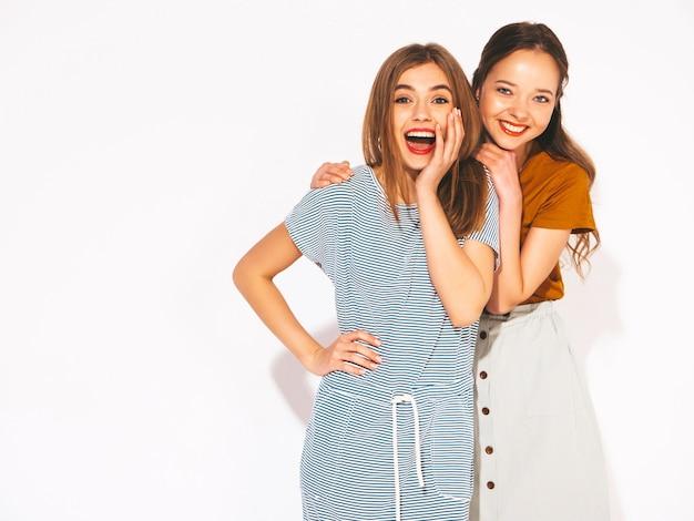 トレンディな夏のカジュアルな服で2人の若い美しい笑顔の女の子。セクシーな屈託のない女性。ショックと驚き