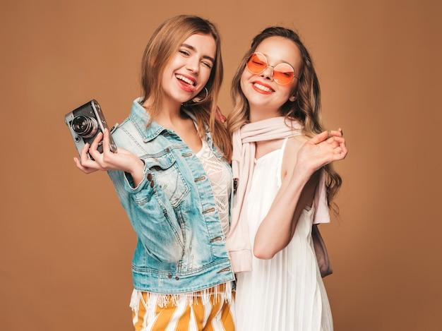 トレンディな夏のカジュアルな服とサングラスで2人の若い美しい笑顔の女の子。セクシーな屈託のない女性がポーズします。レトロなカメラで写真を撮る