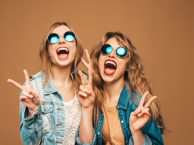 トレンディな夏のジーンズの服とサングラスで2人の若い美しい笑顔の女の子。セクシーな屈託のない女性がポーズします。ピースサインを示す肯定的な悲鳴モデル